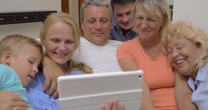 Big family watching video on digital tablet. Family of parents, child and grandparents attracted to the touch pad. They watching entertaining video and laughing stock video
