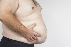 Big fat belly. Man holding his big fat belly isolated on white background Royalty Free Stock Photography