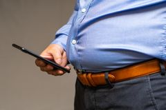 Big fat belly of a Japanese male in a blue shirt, holding a mobile phone. Metabolic Japanese male, close-up of a big fat belly Royalty Free Stock Photo