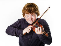 Big fat red-haired boy with small violin. Dmensions mismatch Royalty Free Stock Images