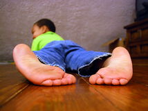 Big Feet. A young boy lies barefoot on a hardwood floor .  His feet are big for his size Royalty Free Stock Photography