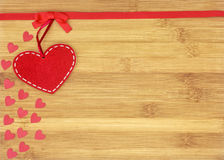 Big felt heart and small hearts on wooden background. Big felt heart and small heartson red background for valentines day, suitable for greeting card, restaurant stock image