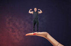 Big female hand holding sportsman with his arms showing muscles Stock Image