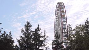 Big ferris wheel in the background of cirrus clouds and pine trees. Side view stock video
