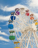 Big ferris wheel with colourful gondolas against blue sky Stock Image