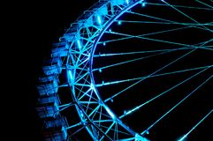 Big ferris wheel with festive blue illumination. Amusement park at night - big ferris wheel with festive blue illumination against night sky. Bottom view Royalty Free Stock Photos