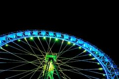 Big ferris wheel with festive green and blue illumination. Against night sky. Bottom view Royalty Free Stock Photography