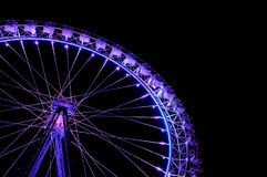 Big ferris wheel with festive purple illumination. Against dark night sky. Side view Royalty Free Stock Images
