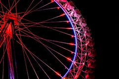 Big ferris wheel with festive red illumination against night sky. Big ferris wheel with festive red illumination against dark night sky.  Side view Royalty Free Stock Photo