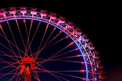 Big ferris wheel with festive red and purple illumination. Against dark night sky. Side view Royalty Free Stock Photo