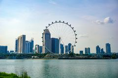 Big ferris wheel in the modern city skyline and bay water on front, Singapore stock images