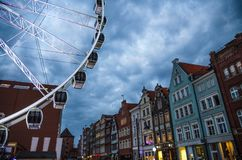 Big ferris wheel, tower, traditional typical facades of colorful buildings at pedestrian Stagiewna street at sunset, dusk, royalty free stock images