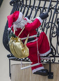 Big figurine of Santa Claus attached to a house's balcony so as Stock Photo