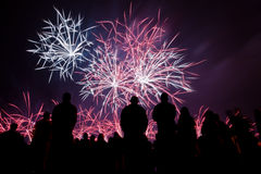 Big fireworks with silhouetted people watching. Big fireworks with silhouetted people in the foreground watching Royalty Free Stock Photography