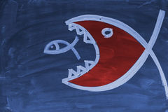 A big fish. Eating a smaller fish drawn with chalk on a blackboard Royalty Free Stock Photography