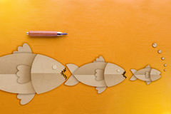 Big fish eat little fish business concepts. With wooden pencil on yellow leather background Stock Photos
