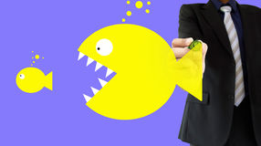 Big fish eat small fish. Businessman is drawing the concept of big fish eating the little fish writing on a wipeboard royalty free stock image