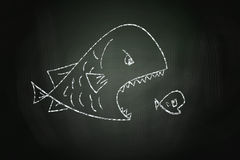 Big Fish Eating Small Fish. Drawn with Chalk on Blackboard Stock Photo