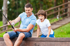 It is a big fish!. Happy father and son fishing together while little boy looking excited and keeping mouth open stock photo