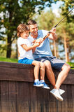 It is a big fish!. Happy father and son fishing together while sitting on quayside Royalty Free Stock Image