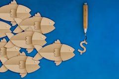 Big fish leader eating money dollar sign bait. Hanging on hook on fishing line Stock Images