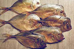 Big fishes on the wood view from the top. Smoked big fish Vomero and one small fish  on wooden background Stock Photos