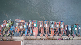 Big fishing boats standing at the sea in Phuket, Thailand. Aeria. Row of fishing boats standing at the sea in Phuket, Thailand. Aerial view from flying drone Stock Photos
