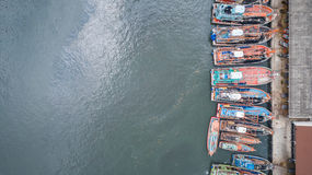 Big fishing boats standing at the sea in Phuket, Thailand. Aeria. Row of fishing boats standing at the sea in Phuket, Thailand. Aerial view from flying drone Stock Images