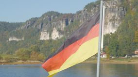 Germany flag close up. Big flag of Germany against river and mountains stock footage