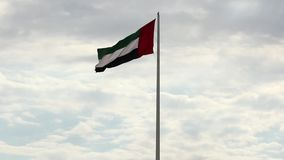 A big flag of UAE flying high on the city of Sharjah, UAE. A National Day celebration on 2nd December. A United Arab Emirates flag flying against clean and stock video