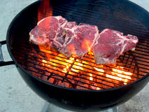 Big Flame Flair Under T-Bones. T-Bone steak on the outdoor barbecue grill with large flair-up Royalty Free Stock Photo