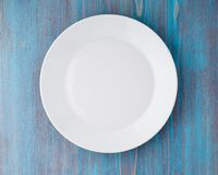 Big flat empty white plate on blue wooden table, top view. Big flat empty white plate on a blue wooden table, top view Stock Images