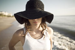 Big Floppy Hat. A beautiful woman at the beach wears a big floppy hat that covers her eyes. Canon 5D Royalty Free Stock Image