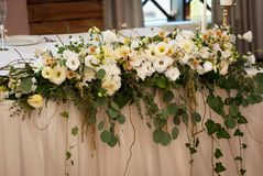 Big flower Arrangement or Composition on Wedding White Table. Rustic Style Decor with Flowers. Big flower Arrangement or Composition on Wedding White Table Stock Photo