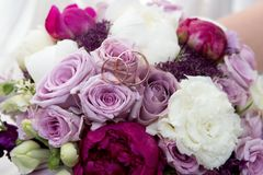 Big flower bouquet. Big Bouquet and Two Wedding Rings. Goods for wedding. This photo is perfect for magazines, shops dealing with wedding dresses ceremonies Royalty Free Stock Image