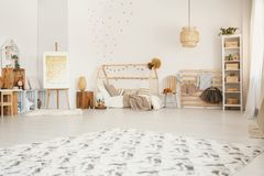 Big fluffy carpet placed on the floor in white Scandinavian style kid room interior with wooden furniture and home-shape bed. Big fluffy carpet placed on the stock photography