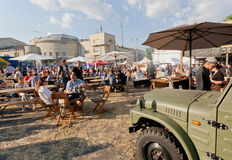 Big food-court with tables and people eating meals under umbrelas outdoor Royalty Free Stock Photo
