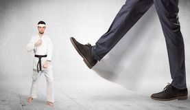Big foot trample karate trainer concept. Big foot trample young karate trainer conceptn royalty free stock photo