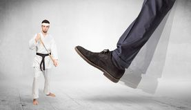 Big foot trample karate trainer concept. Big foot trample young karate trainer conceptn royalty free stock images
