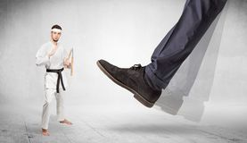 Big foot trample karate trainer concept. Big foot trample young karate trainer concept royalty free stock image