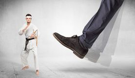 Big foot trample karate trainer concept. Big foot trample young karate trainer concept royalty free stock photography