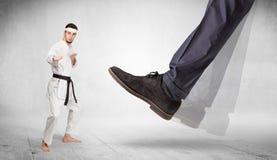 Big foot trample karate trainer concept. Big foot trample young karate trainer concept stock photos