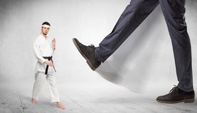 Big foot trample karate trainer concept. Big foot trample young karate trainer conceptn royalty free stock photography