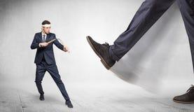 Big foot trample suited karate man. Big foot trample young suited karate man stock photography