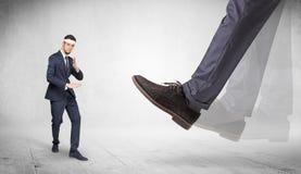 Big foot trample suited karate man. Big foot trample young suited karate man stock photos