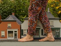 Big foots and small houses.Unusual view.Gulliver in town. stock photography