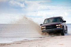 Big four-wheel car. Driving on sandy sea coast in water splashes Royalty Free Stock Image