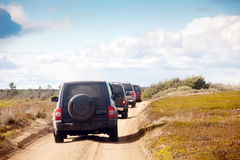 Big four-wheel cars in a row. Four big four-wheel cars in a row on sandy road on scenic nature background Royalty Free Stock Photos