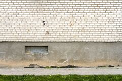 Big fragment of white brick wall with green grass Stock Photos