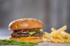 Big fresh appetizing burger with pepper and potatoes Stock Images